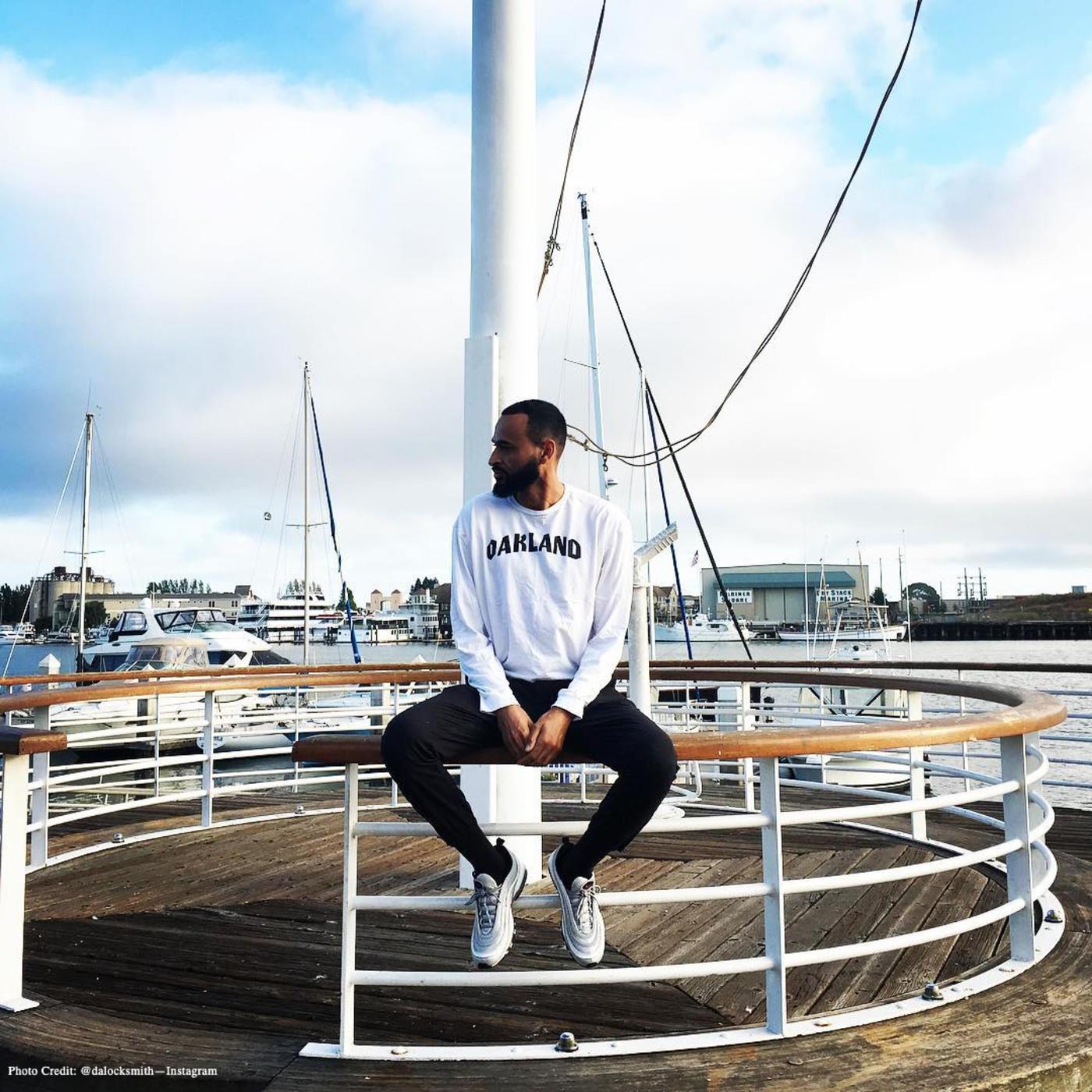 Man sitting on a railing wearing a black and white Oakland Sweatshirt