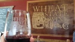 A Wine sample held up in front of a Wheat State Wine Co sign in Winfield, KS