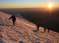 4 climbers ascending Mt. Rainier during sunset