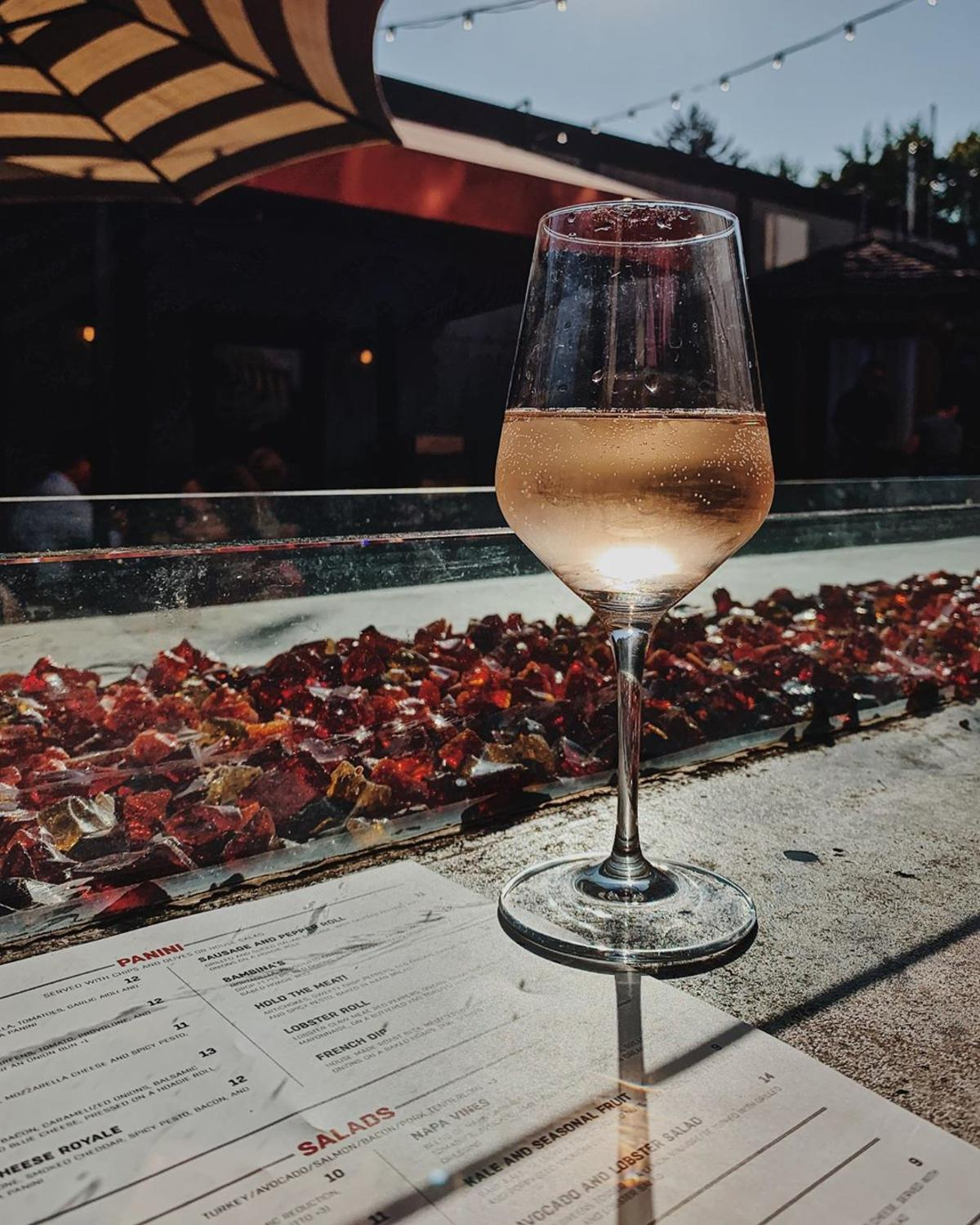 A glass of wine by the outdoor firebar on the patio of Prost! Wine Bar & Charcuterie in Frankenmuth