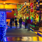 People strolling on sidewalk amongst the holiday lights display at the Columbus Commons