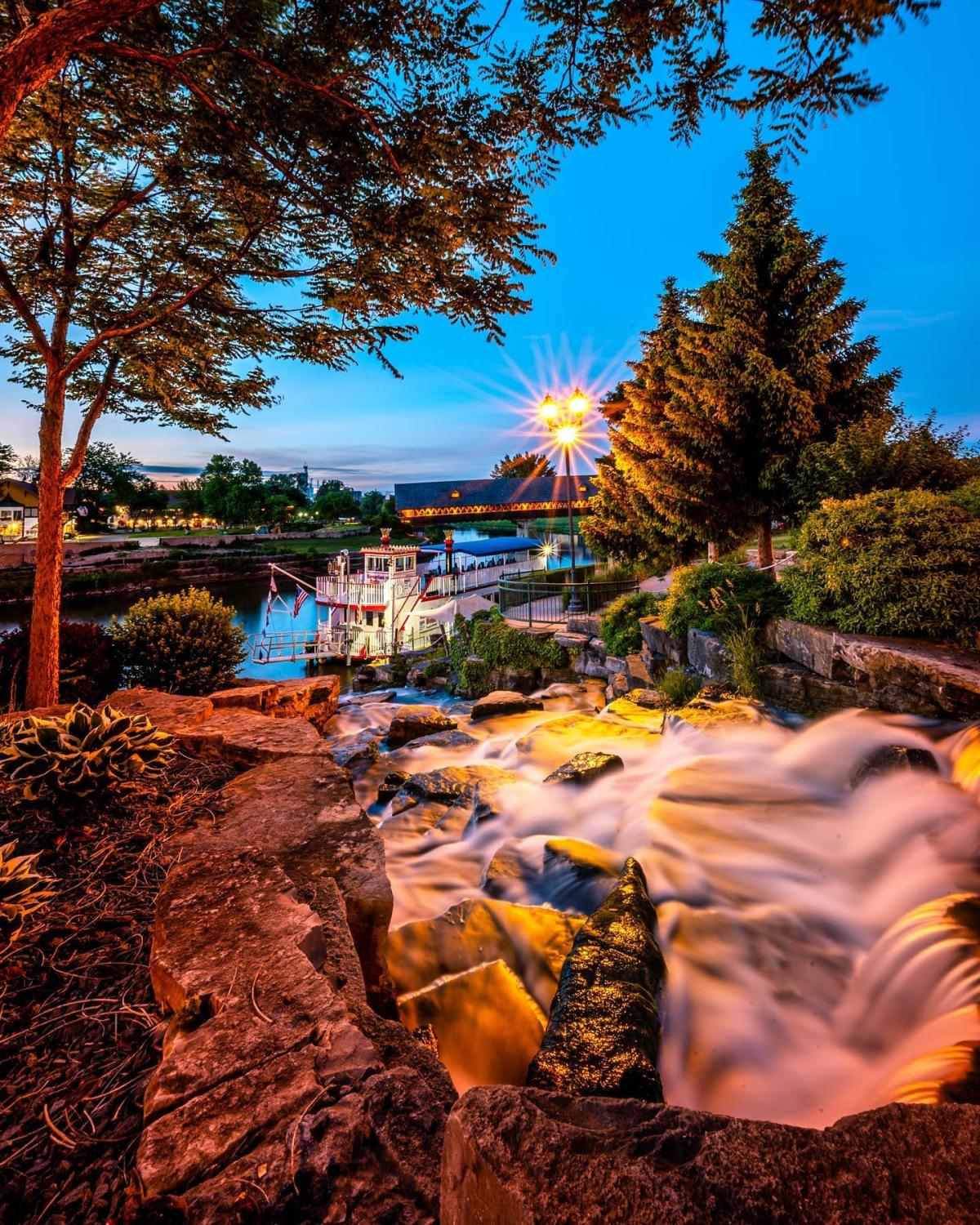 Bavarian Belle Riverboat docked by the Frankenmuth River Place Shops waterfalls at dusk