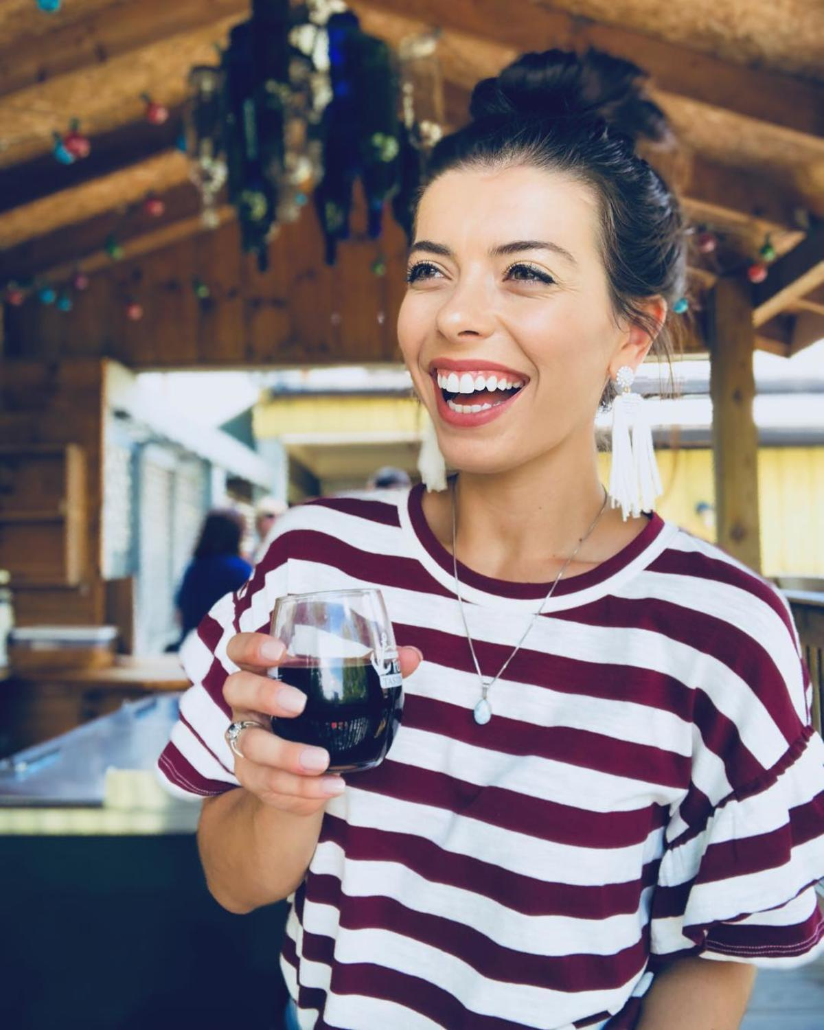 Young woman smiling and laughing while wine tasting at Frankenmuth FunShips