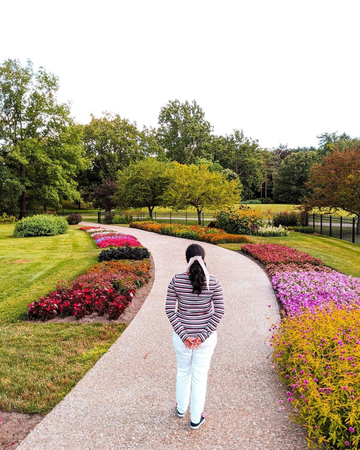 Woman looking down a flower-lined pathway winding through Dow Gardens in Midland