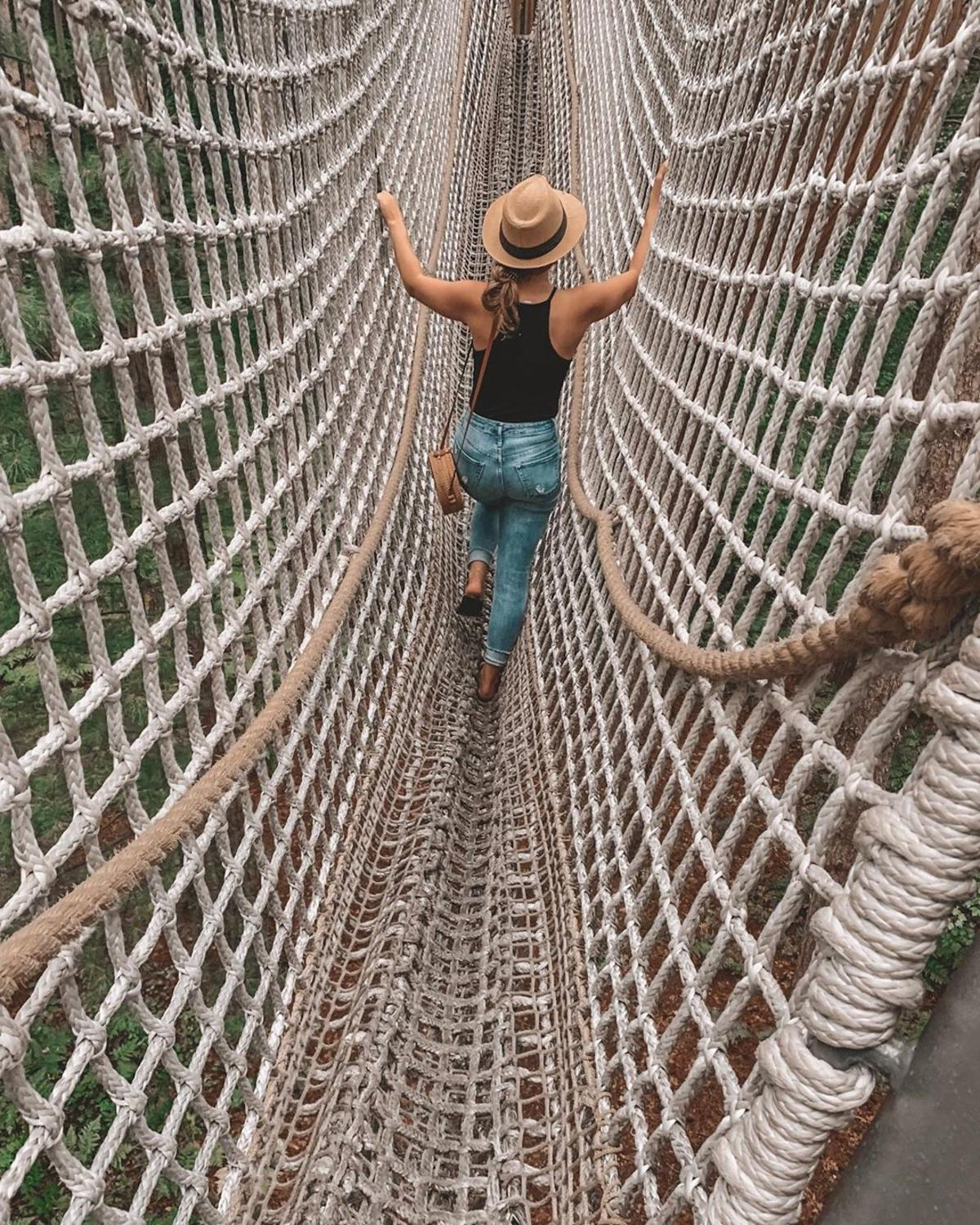 Young woman climbing across the cargo net bridge at Whiting Forest of Dow Gardens
