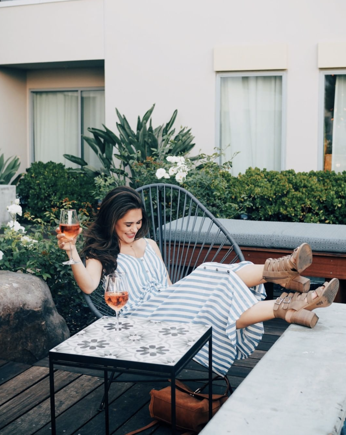 A smiling woman enjoying a glass of wine in the outdoor seating area of the Kimpton Shorebreak Resort in Huntington Beach California