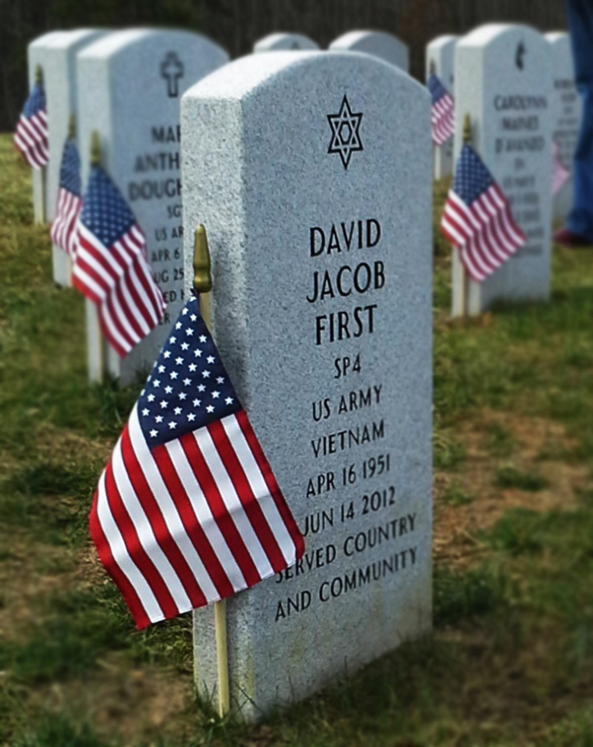 headstones at a cemetery with American flags next to the headstones