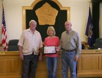 NANEEN AND RICHARD DROSSE receive a Tourism Ambassador Award from Edwin Lighthall (left), chairman of the Oswego County Tourism Advisory Council. They have organized water chestnut removal projects, Earth Day cleanups, Great Bear Farm trail expansion, and community events in Minetto for several years.