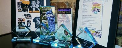 A display of Johnston County Visitors Bureau marketing samples with awards won in front of them.