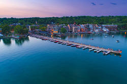 Overhead drove shot of Skaneateles Lake, Village and Pier at dusk