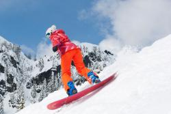 A snowboard bunny carving up the slope at Summit West Snoqualmie