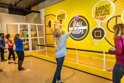 "Adults and children shooting basketball hoops inside the ""Ohio - Champion of Sports"" exhibit at Ohio History Center"