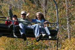 A family waves from the chairlift at Bristol Mountain during a fall skyride