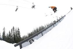 Snowboarding catching air above a rail on the slope