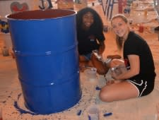 Photo of two teen girls paint a drum