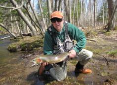 Fran Verdoliva, Salmon River Program Coordinator for the DEC, holds a nice spring steelhead. The fish was released back into the river. (Photo by Jessica Burt, Oswego County Tourism Office.)