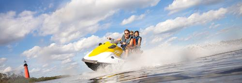 A family is enjoying a jetski experience in Ponce Inlet with a view of Ponce Inlet Lighthouse.