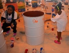 Photo of little girl and month painting a drum