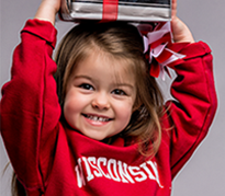 A young girl wearing UW apparel holds books over her head