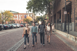 A group of four friends walk the brick roads of Old Town in Wichita