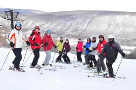 A group of skiers pose at the top of Bristol Mountain