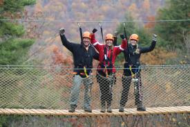 A group of hikers pose while on a zip lining course at Bristol Mountain Aerial Adventures