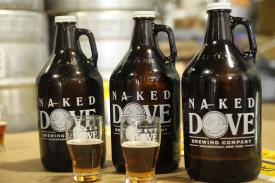 Bottles of Naked Dove beer sit on a table inside of Naked Dove Brewing