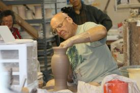 A man makes a pot inside of Wizard of Clay pottery in Bristol