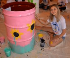 Photo of teen girl painting a drum.