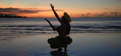 A dancer performing a traditional Chamorro dance at sunset on a Guam beach