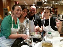 A group of friends pose with a chef after making a meal at the New York Kitchen