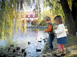Two small children feed the ducks at Children's Lake in Boiling Springs, PA.