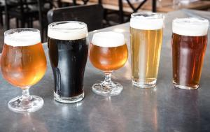 Craft beers of multiple varieties and colors in different glasses on countertop