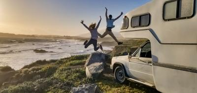 man and woman jumping in excitement next to their RV