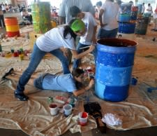 Photo of three teens painting a drum