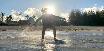 Skim Boarder coasting along the waves in Guam