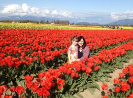 smiling mom and young daughter posing between rows of tulips in Skagit Valley
