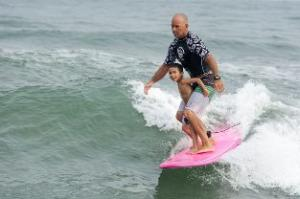 Surfer on pink surfboard with child