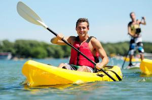 A man smiles to the camera while kayaking on Canandaigua lake during a hot summer day