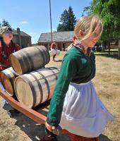 Two young girls at Fort Nisqually dress in period clothing for living history