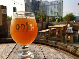 Glass or orange beer with Odin logo in front of Hotel Interurban