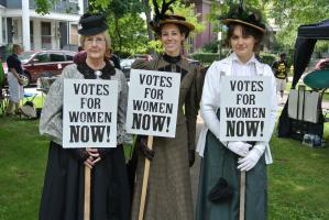 three women hold votes for women now signs