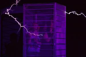 stand in a cage during the Electricity Theatre show