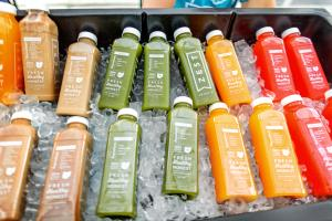 Various bottles of pressed juice from Zest in cooler of ice
