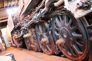 A close-up photo of the wheels of a steam train.