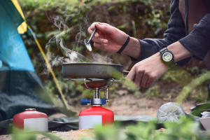 Person Cooking Over A Campfire
