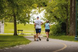 Pair Of Ohio River Greenway Runners With A Small Dog
