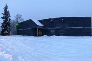 panoramic exterior of a dark two-story building in winter