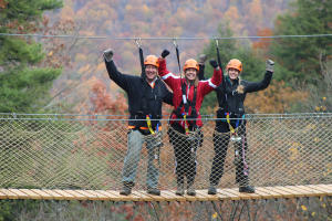 A group of zip liners pose for a photo on a bridge at Bristol Mountain Aerial Adventures