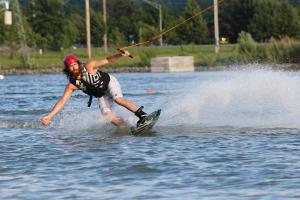A wakeboarder splashes water with his board at Roseland Wake Park in Canandaigua